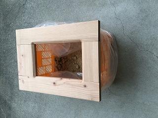 竹パウダーで消臭:コンテナに木の便座を載せ,中に竹パウダーを入れた簡易トイレ